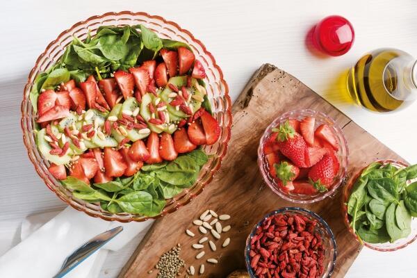 Blattspinatsalat mit Gojibeeren, Erdbeeren, Pinienkernen, Kiwi und Hanfsamen