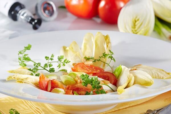 Lauwarmer Chicoréesalat mit Frühlingslauch, Tomaten und Pinienkernen